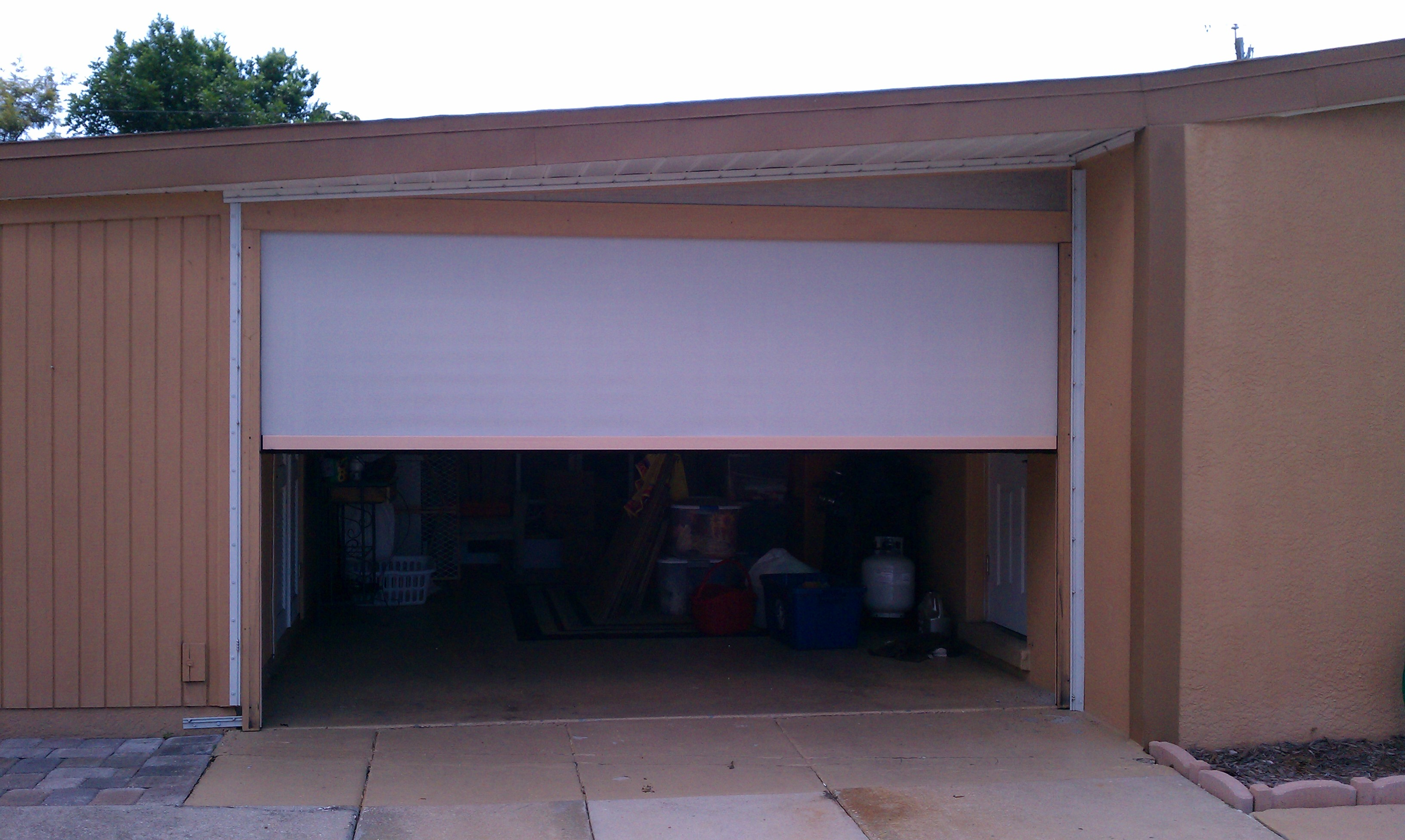 Garage doors gulf coast retractable screens for Motorized garage door screens